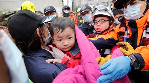 In this Saturday, Feb. 6, 2016 photo, a baby boy is rescued from a collapsed building after an earthquake in Tainan, Taiwan. A powerful, shallow earthquake struck southern Taiwan before dawn Saturday. (AP Photo/Wally Santana, File)