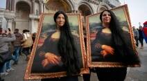 Two carnival revellers masquerade as Leonardo da Vinci's painting 'Mona Lisa' pose in St. Mark's Square in Venice, Italy, Sunday, Jan. 31, 2016. Carnival-goers in Venice are being asked by police to momentarily lift their masks as part of new anti-terrorism measures for the annual festivities. (AP Photo/Domenico Stinellis)