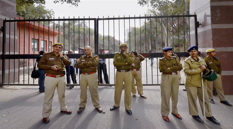 New Delhi: Police personnel guard at the entrance of JNU where students are agitating, in New Delhi on Monday. PTI Photo by Kamal Singh (PTI2_15_2016_000197B)