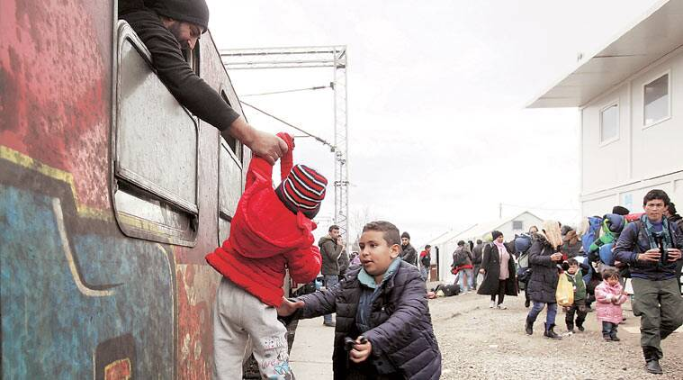 A refugee passes a baby from a train window to a boy, upon their arrival at the transit center for Syrian refugees near the northern Macedonian village of Tabanovce, before continuing their journey to Serbia. AP