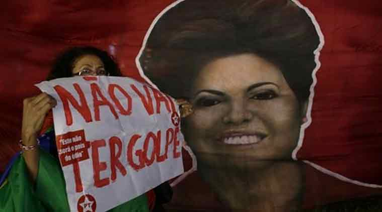 "Woman shows poster written in Portuguese ""There will not be a coup"" next to a picture of Brazil's President Dilma Rousseff, during a rally in her support and of former President Luiz Inacio Lula da Silva, in Brasilia, Brazil. (Source: AP)"