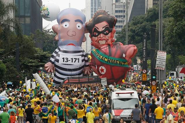 """Demonstrators parade large inflatable dolls depicting Brazil's former President Luiz Inacio Lula da Silva in prison garb and current President Dilma Rousseff dressed as a thief, with a presidential sash that reads """"Impeachment,"""" in Sao Paulo, Brazil, Sunday, March 13, 2016. The corruption scandal at the state-run oil giant Petrobras has ensnared key figures from Rousseff's Workers' Party, including her predecessor and mentor, Lula da Silva, as well as members of opposition parties. (AP Photo/Andre Penner)"""