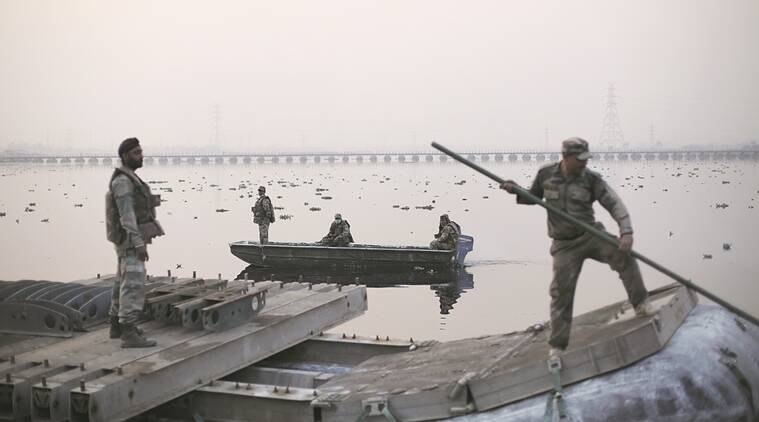 Military personnel transport an inflatable float meant for the pontoon bridge over Yamuna near the site of the World Culture Festival 2016 along the Yamuna flood plains on Tuesday (the pontoon bridge on the background was the first bridge constructed by the UP PWD for the event). Express photo by Oinam Anand