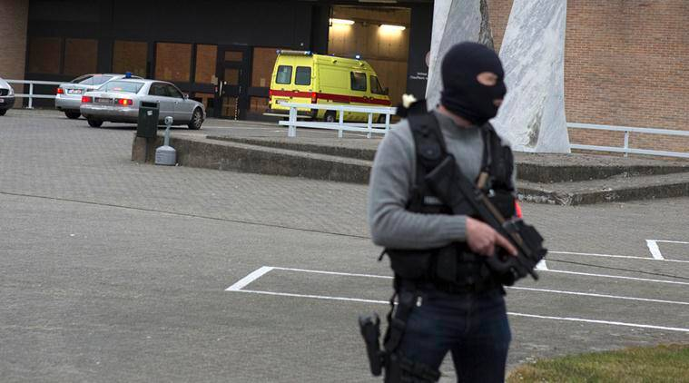 A special forces police officer guards as a police convoy and ambulance thought to be carrying captured fugitive Salah Abdeslam arrives at the federal penitentiary in Bruges, Belgium. AP Photo