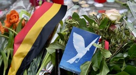 A picture of a dove is placed beside candles and flowers for the victims of the bombings at the Place de la Bourse in the center of Brussels, Wednesday, March 23, 2016. Bombs exploded yesterday at the Brussels airport and one of the city's metro stations Tuesday, killing and wounding scores of people, as a European capital was again locked down amid heightened security threats. (AP Photo/Martin Meissner)