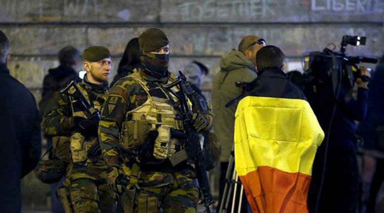 Belgian soldiers patrol as people pay tribute to the victims of Tuesday's bomb attacks at the Place de la Bourse in Brussels, Belgium, March 26, 2016.  REUTERS/Francois Lenoir