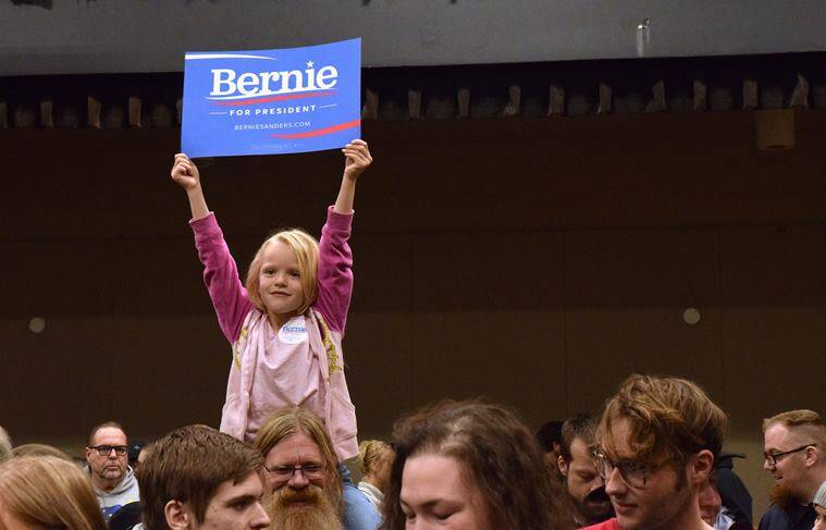 """Five-year-old Courtney Skinner holds up a """"Bernie Sanders for President"""" sign while sitting on Tom Skinner's shoulders at the Juneau Democratic Caucus on Saturday, March 26, 2016, in Centennial Hall's Sheffield Ballroom in Juneau, Alaska. Sanders won Democratic presidential caucuses in Alaska on Saturday, a victory he hopes will stoke a spring comeback against the commanding front-runner, Hillary Clinton. (James Brooks/The Juneau Empire via AP) MANDATORY CREDIT"""