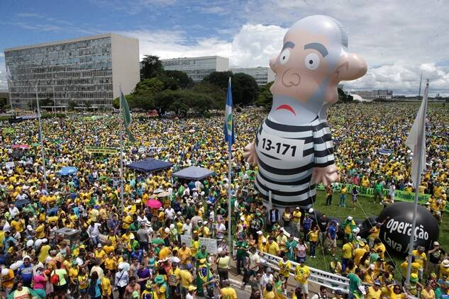 Demonstrators demand the impeachment of Brazil's President Dilma Rousseff during a rally where a large inflatable doll depicts former President Luiz Inacio Lula da Silva in prison garb in Brasilia, Brazil, Sunday, March 13, 2016. The corruption scandal at the state-run oil giant Petrobras has ensnared key figures from Rousseff's Workers' Party, including her predecessor and mentor, Lula da Silva, as well as members of opposition parties. (AP Photo/Eraldo Peres)