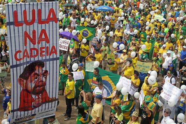 """A poster with a picture of Brazil's former President Luiz Inacio Lula da Silva  behind bars carries the message in Portuguese: """"Lula in chains""""  during a protest demanding the impeachment of Brazil's current President Dilma Rousseff in Brasilia, Brazil, Sunday, March 13, 2016. The corruption scandal at the state-run oil giant Petrobras has ensnared key figures from Rousseff's Workers' Party, including her predecessor and mentor, Lula da Silva, as well as members of opposition parties. (AP Photo/Eraldo Peres)"""
