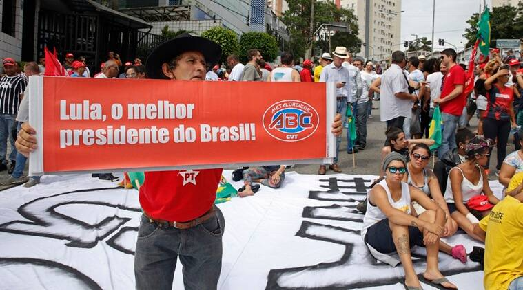 """A man holds a banner that reads in Portuguese: """"Lula, the best President of Brazil!"""" alongside other supporters of Brazil's former President Luiz Inacio Lula da Silva outside his residence in the Sao Bernardo do Campo area of Sao Paulo, Brazil, on the same day as nationwide protests demand the impeachment of current President Dilma Rousseff, Sunday, March 13, 2016. The corruption scandal at the state-run oil giant Petrobras has ensnared key figures from Rousseff's Workers' Party, including her predecessor and mentor, Lula da Silva, as well as members of opposition parties. (AP Photo/Andre Penner)"""