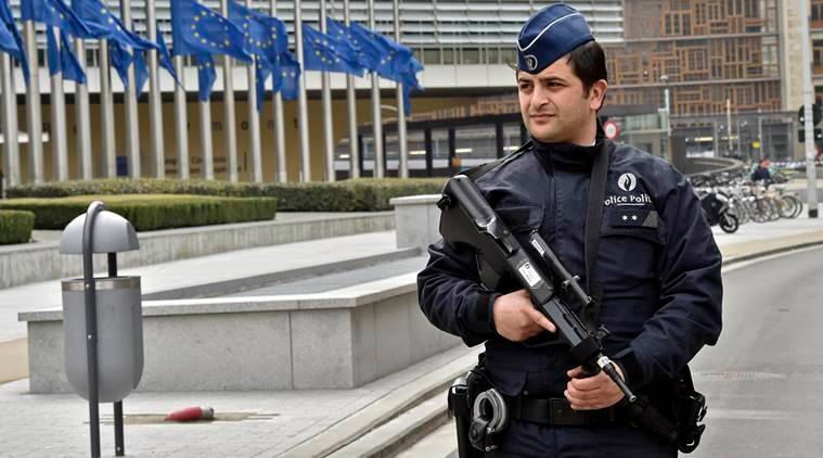 Police patrol the EU commission building, after  a bomb exploded nearby, at the subway in Brussels, Belgium, Tuesday, March 22, 2016. Authorities locked down the Belgian capital on Tuesday after explosions rocked the Brussels airport and subway system, killing  a number of people and injuring many more. Belgium raised its terror alert to its highest level, diverting arriving planes and trains and ordering people to stay where they were. Airports across Europe tightened security. (AP Photo/Martin Meissner)