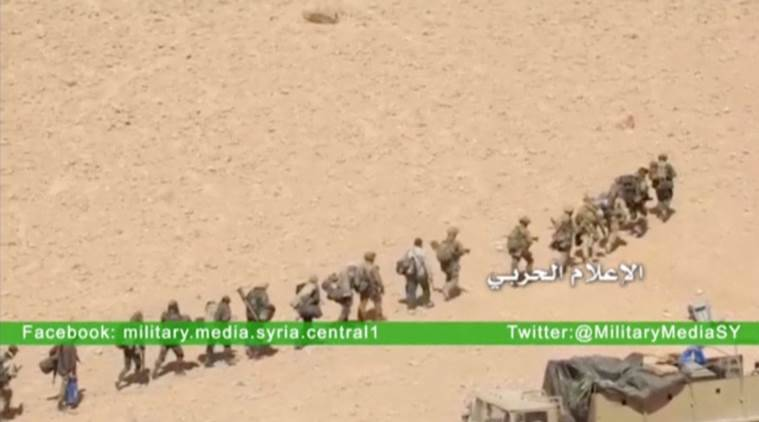 Soldiers march in a line at where the Syrian military media said is Palmyra, in this still image taken from a Syrian military media video uploaded on March 23, 2016, as Syrian government forces push their way into Palmyra while the army attempts to recapture the historic city from Islamic State. REUTERS/Syrian Military Media via Reuters TV ATTENTION EDITORS - THIS PICTURE WAS PROVIDED BY A THIRD PARTY. REUTERS IS UNABLE TO INDEPENDENTLY VERIFY THE AUTHENTICITY, CONTENT, LOCATION OR DATE OF THIS IMAGE. EDITORIAL USE ONLY. NOT FOR SALE FOR MARKETING OR ADVERTISING CAMPAIGNS. NO RESALES. NO ARCHIVE. THIS PICTURE IS DISTRIBUTED EXACTLY AS RECEIVED BY REUTERS, AS A SERVICE TO CLIENTS.