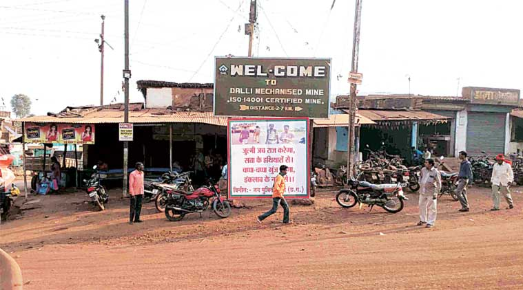 A man walks past a poster showing Dr Saibal Jana being led by a policeman, at one of Dalli-Rajhara's three chowks. (Express Photo)