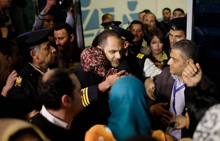 An Egyptian crew member of the hijacked domestic EgyptAir flight is hugged by his relatives upon the flight arrival at Cairo International airport, Egypt, Tuesday, March 29, 2016. An Egyptian man wearing a fake explosives belt who hijacked a domestic EgyptAir flight and forced it to land in Larnaca Cyprus on Tuesday has surrendered and was taken into custody after he released all passengers and crew unharmed. (AP Photo/Amr Nabil)