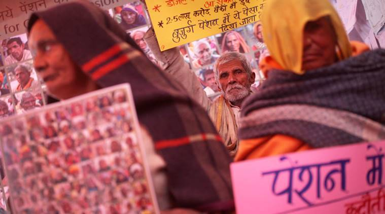 Senior citizens hold placard that has photographs of fellow protestors and PM Manmohan Singh, Congress Chief Sonia Gandhi, Montek Singh Ahluwalia seeking increased pension for senior citizens near Jantar mantar on Friday. Express photo by Oinam Anand. 20 December 2013