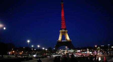 People walk towards the illuminated Eiffel Tower illuminated with the Belgium national colors black, yellow and red in honor of the victims of the today's attacks at the airport and the metro station in Brussels, in Paris, Tuesday, March 22, 2016. Explosions, at least one likely caused by a suicide bomber, rocked the Brussels airport and its subway system Tuesday, prompting a lockdown of the Belgian capital and heightened security across Europe. (AP Photo/Thibault Camus)