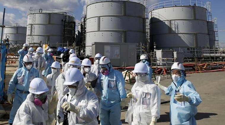 "Members of the media, wearing protective suits and masks, walk after receiving a briefing from Tokyo Electric Power Co. (TEPCO) employees (in blue) in front of storage tanks for radioactive water at TEPCO's tsunami-crippled Fukushima Daiichi nuclear power plant in Okuma town, Fukushima prefecture, Japan in this February 10, 2016 file photo. The robots sent in to find highly radioactive fuel at Fukushima's nuclear reactors have ""died""; a subterranean ""ice wall"" around the crippled plant meant to stop groundwater from becoming contaminated has yet to be finished. And authorities still don't how to dispose of highly radioactive water stored in an ever mounting number of tanks around the site. REUTERS/Toru Hanai/Files"