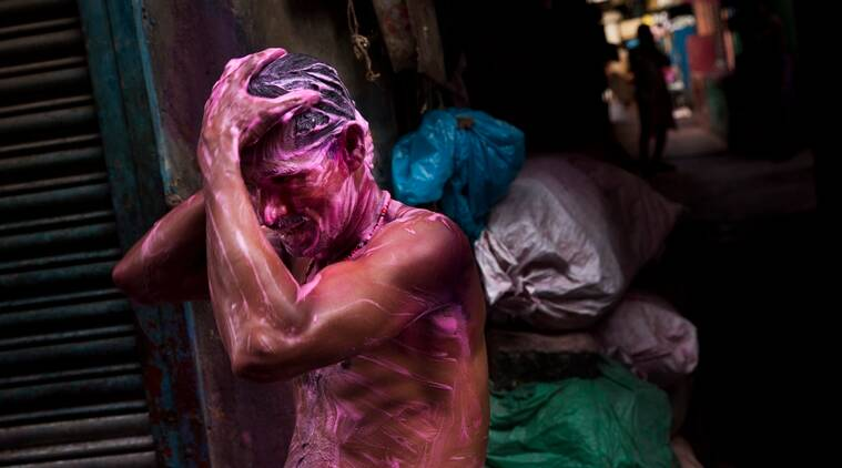 An Indian man takes a bath to clear Holi color powder on him in central Kolkata, India, Monday, March 21, 2016. The colorful holiday, celebrated mainly in India and Nepal, marks the beginning of spring and the triumph of good over evil. (AP Photo/Bernat Armangue)