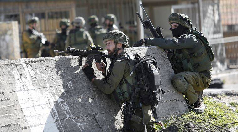 FILE - In this Monday, Feb. 15, 2016 file photo, Israeli soldiers take positions during a raid to arrest a Palestinian at the Amari Palestinian refugee camp, near the West Bank city of Ramallah during clashes with Palestinians that erupted after they entered the camp early in the morning. Palestinian officials say Israeli military raids in Palestinian-controlled territory have dramatically increased since a wave of violence erupted five months ago _ undermining the public's trust in their own security forces and jeopardizing one of the last areas of official contact between Israel and the Palestinians. (AP Photo/ Nasser Shiyoukhi, File)