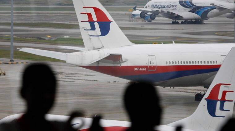 In this photo taken on Saturday, March 5, 2016, Malaysia men are silhouetted against taxied Malaysia Airlines' planes in Kuala Lumpur International Airport in Sepang, Malaysia. Malaysia's transport minister said on Monday, March 14, 2016, that two plane pieces found in Mozambique will be sent to Australia to verify if they belong to Malaysia Airlines Flight 370. (AP Photo/Joshua Paul)