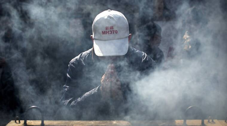 A man wearing an MH370 hat prays with relatives of passengers aboard missing Malaysia Airlines Flight 370 at the Lama Temple in Beijing, Tuesday, March 8, 2016. Tuesday marked the second anniversary of the disappearance of MH370, which vanished March 8, 2014 while en route from Kuala Lumpur to Beijing. (AP Photo/Mark Schiefelbein)