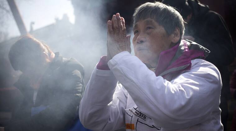 A woman wearing an MH370 shirt prays with relatives of passengers aboard missing Malaysia Airlines Flight 370 at the Lama Temple in Beijing, Tuesday, March 8, 2016. Tuesday marked the second anniversary of the disappearance of MH370, which vanished March 8, 2014 while en route from Kuala Lumpur to Beijing. (AP Photo/Mark Schiefelbein)