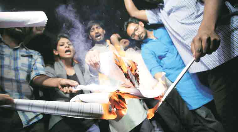 JNU students burn photocopies of select verses of the 'Manusmriti' Tuesday. (Express Photo: Praveen Khanna)