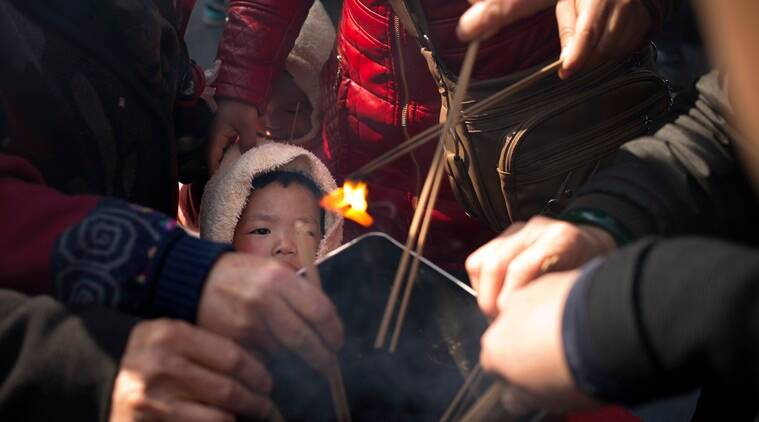 A child watches while relatives of passengers aboard missing Malaysia Airlines Flight 370 light incense sticks at the Lama Temple in Beijing, Tuesday, March 8, 2016. Tuesday marked the second anniversary of the disappearance of MH370, which vanished March 8, 2014 while en route from Kuala Lumpur to Beijing. (AP Photo/Mark Schiefelbein)