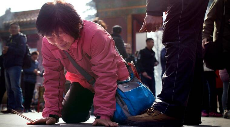 A woman cries and drops to her knees while praying and burning incense with relatives of passengers aboard missing Malaysia Airlines Flight 370 at the Lama Temple in Beijing, Tuesday, March 8, 2016. Tuesday marked the second anniversary of the disappearance of MH370, which vanished March 8, 2014 while en route from Kuala Lumpur to Beijing. (AP Photo/Mark Schiefelbein)