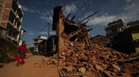 A woman waks past a ruined home from the recent earthquake in Charikot in Nepal on thursday. Express Photo by Tashi Tobgyal New Delhi 140515
