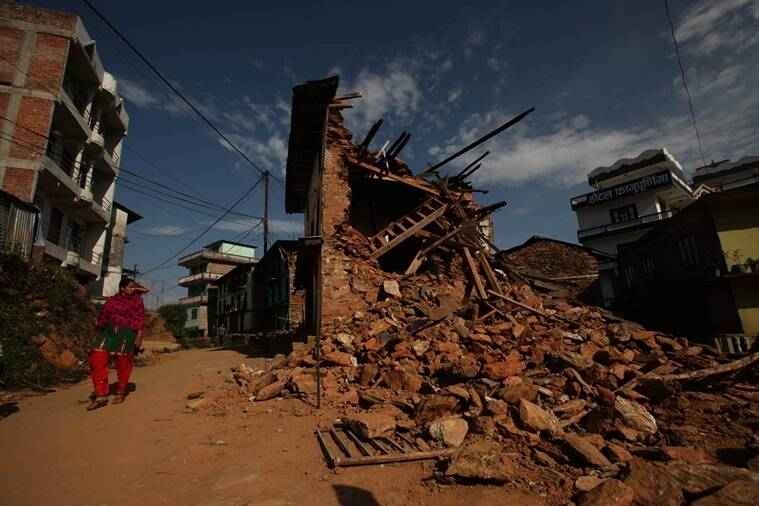 A woman waks past a ruined home from the recent earthquake in Charikot in Nepal. File/Express Photo/Tashi Tobgyal