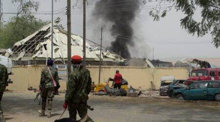 Nigerian soldiers patrol outside the site of an accidental explosion in Yola, Nigeria, Thursday, Feb. 25, 2016. Bombs retrieved from Boko Haram exploded accidentally Thursday at police headquarters in Nigeria's northeastern city of Yola, killing four people and wounding a score of officers and school children cut by shattered glass, officials said. (AP Photo)