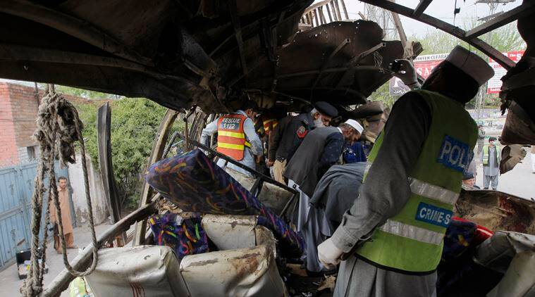 Pakistani security personnel examine a bus following a bomb blast in Peshawar, Pakistan, Wednesday, March 16, 2016. A bomb ripped through a bus carrying Pakistani government employees in the northwestern city of Peshawar on Wednesday, police said. (AP Photo/Mohammad Sajjad)