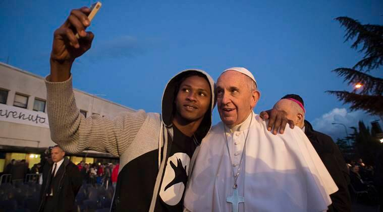 Pope Francis poses for a selfie during his visit at the Castelnuovo di Porto refugees center, some 30km (18, 6 miles) from Rome, Thursday, March 24, 2016. The pontiff washed and kissed the feet of Muslim, Orthodox, Hindu and Catholic refugees Thursday, declaring them children of the same God, in a gesture of welcome and brotherhood at a time when anti-Muslim and anti-immigrant sentiment has spiked following the Brussels attacks. (L'Osservatore Romano/Pool Photo via AP)