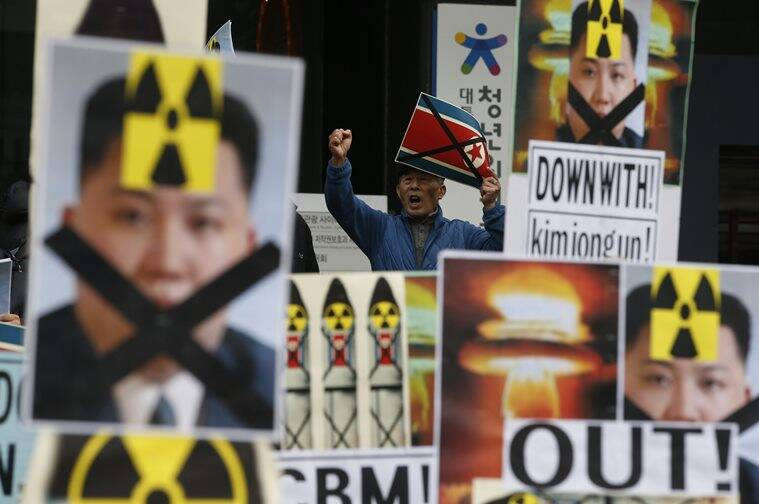 A South Korean man holding a crossed North Korean flag shouts slogans among placards with crossed portraits of North Korean leader Kim Jong Un pasted with the radiation warning symbol during an anti-North Korea rally in downtown Seoul. AP Photo