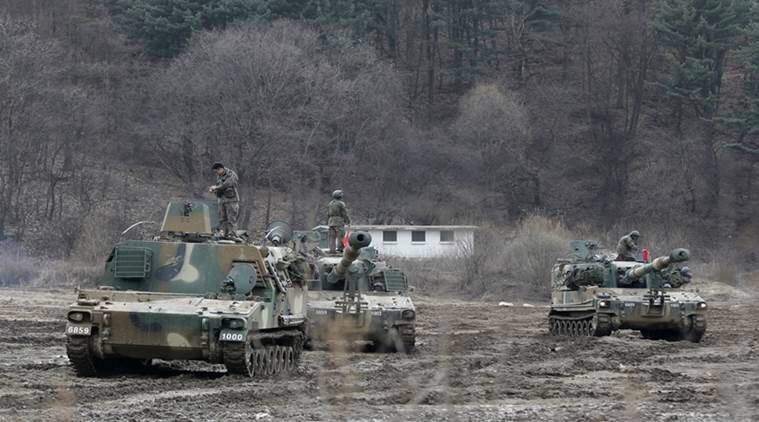 """South Korean army soldiers stand on their K-55 self-propelled howitzers during an annual exercise in Paju, near the border with North Korea, Monday, March 7, 2016. North Korea on Monday issued its latest belligerent threat, warning of an indiscriminate """"pre-emptive nuclear strike of justice"""" on Washington and Seoul, this time in reaction to the start of huge U.S.-South Korean military drills. (AP Photo/Ahn Young-joon)"""