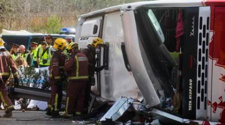 Emergency services personnel stand at the scene of a bus accident crashed on the AP7 highway that links Spain with France along the Mediterranean coast near Freginals halfway between Valencia and Barcelona early Sunday, March 20, 2016. A bus carrying university students back from a fireworks festival crashed Sunday on a main highway in northeastern Spain, killing 14 passengers and injuring 30 others, a Catalonian official said. (AP Photo)