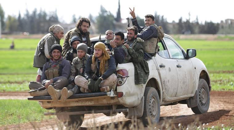 Rebel fighters from 'Jaysh al-Sunna' gesture as they ride a vehicle in Tel Mamo village, in the southern countryside of Aleppo, Syria March 6, 2016. REUTERS/Khalil Ashawi