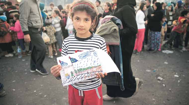 Shaharzad Hassan, 8, whose family fled Aleppo, poses with a drawing she made at an overcrowded refugee camp on the Greece-Macedonia border last week. (Source: AP)