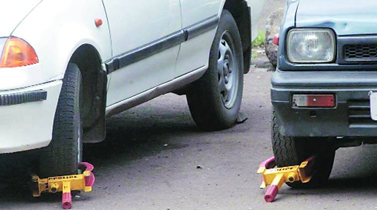 Traffic police are challaning people by using wheel clamps.