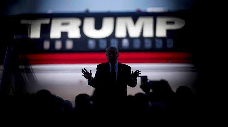Republican presidential candidate Donald Trump is silhouetted against his plane as he speaks during a rally Saturday, Feb. 27, 2016, in Bentonville, Ark., as shot through the crowd. (AP Photo/John Bazemore)