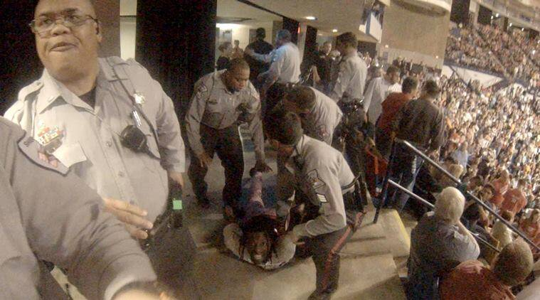 Rakeem Jones lies on the ground while being removed by deputies from a Donald Trump rally in Fayetteville, North Carolina March 9, 2016, in a still image from video provided by Ronnie Rouse March 10, 2016.  Jones was assaulted during his eviction from the rally, and a man faces criminal charges in the altercation.  REUTERS/Ronnie C/Handout via Reuters