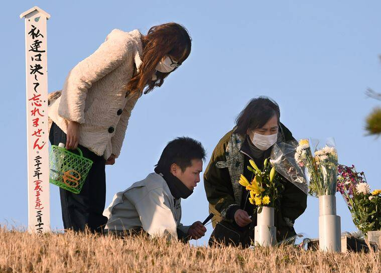 "People offer incense stick to mourn the victims of the deadly March 11, 2011 earthquake and tsunami, in Natori, Miyagi prefecture, northeastern Japan early Friday, March 11, 2016. Japan marks the fifth anniversary of the disaster on Friday. The sign reads ""We never forget."" (Jun Hirata/Kyodo News via AP) JAPAN OUT, MANDATORY CREDIT"