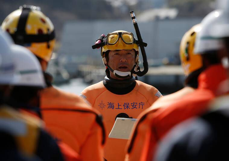 A group leader of Japanese Coast Guard divers briefs his team members before underwater searches Thursday, March 10, 2016, a day before the fifth anniversary of the deadly March 11, 2011 earthquake and tsunami, in Rikuzentakata, Iwate Prefecture, northeastern Japan. The Japanese coast guard has resumed underwater searches for some of the more than 2,500 people still missing from the 2011 disaster that devastated the country's northeast coast. (AP Photo/Koji Ueda)