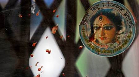 Blood stained glass and a photograph of the Hindu goddess Durga is seen near the spot where three motorcycle-riding assailants hacked student activist Nazimuddin Samad to death while walking with a friend, in Dhaka, Bangladesh, Thursday, April 7, 2016. Police suspect 28-year-old Samad was targeted for his outspoken atheism in the Muslim majority country and for supporting a 2013 movement demanding capital punishment for war crimes involving the country's independence war against Pakistan in 1971, according to Dhaka Metropolitan Police Assistant Commissioner Nurul Amin. (AP Photo)