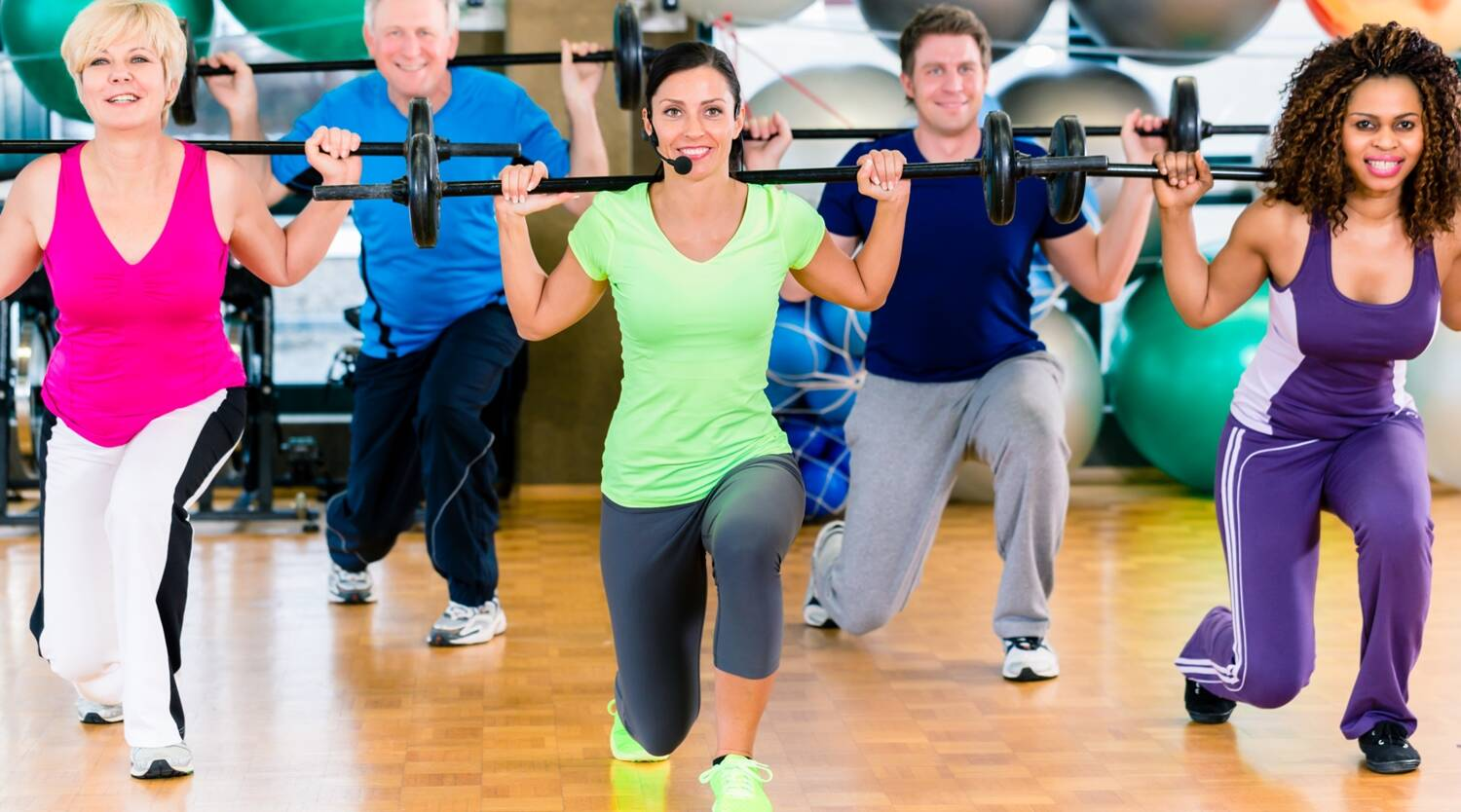 Men and women lifting barbell in gym
