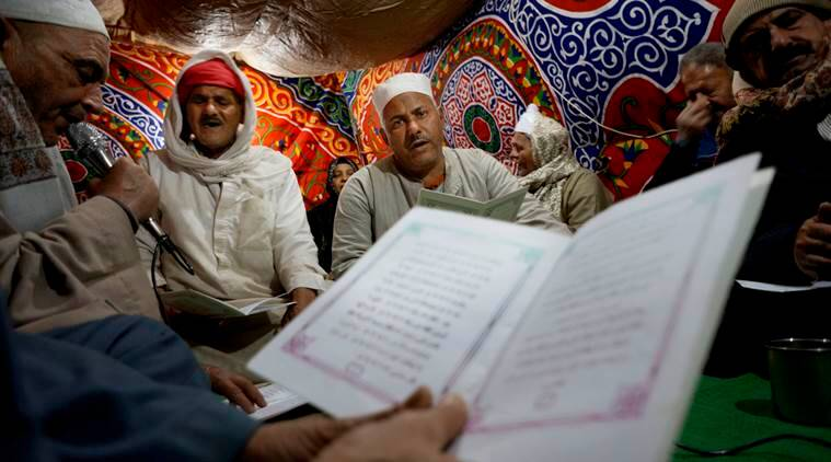 In this Wednesday, March 16, 2016 photo, Muslim men recite parts of the Quran during  the Moulid or birthday, of Sayeda Nafisa, a descendant of the Prophet Muhammad through his grandson Hasan, near the mosque named after her, in Cairo, Egypt. (AP Photo/Amr Nabil)