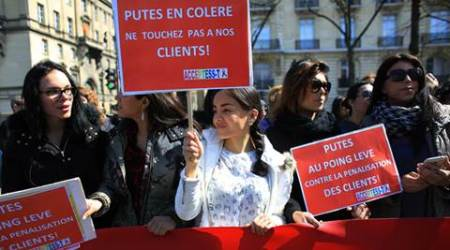 Sex workers hold signs reading 'Prostitutes are angry. Don't touch to our customers' during a protest against new bill against prostitution and sex trafficking, in Paris, Wednesday, April 6, 2016. France's lower house of parliament holds a final vote on Wednesday on a bill against prostitution and sex trafficking that bans buying sex, not selling it. Customers would face fines and be required to attend classes on the harms of prostitution. Opponents fear that cracking down will push prostitutes to hide and they would be even more at the mercy of pimps and violent clients. (AP Photo/Thibault Camus)
