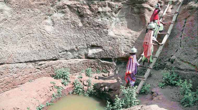 Women collect water from an almost dried-up well at a village in Surgana Taluka, near Nasik, Thursday. PTI