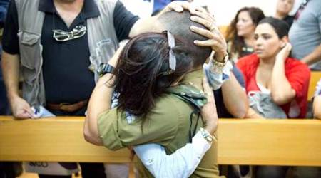 An Israeli solider is hugged by his mother inside an Israeli military court in Tel Aviv, Israel, Monday, April 18, 2016. Israeli Army Radio says the court has indicted the soldier for manslaughter in the fatal shooting of a wounded Palestinian attacker in the West Bank. The soldier, whose name was not released under a gag order, has also been charged with inappropriate military conduct. The shooting took place last month in Hebron, a West Bank city that has been a focal point of a seven-month wave of Israeli-Palestinian violence. (AP Photo/Ariel Schalit)